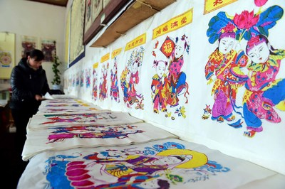 As the New Year approaches, the workshops of the Yangjiabu Woodblock New Year Paintings are getting busy supplying the festival market. In the photo, a worker is sorting out the newly printed New Year paintings.