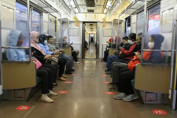Passengers Sits Inside A Train equipped with markers. Before the pandemic, trains were often packed. Now regulations limit the number of passengers to 74 people in each car in order to ensure physical distancing.