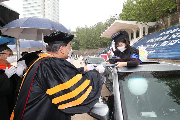 A 2019 graduate who couldn't have a traditional celebration because of the ongoing COVID-19 pandemic is receiving her diploma in car during the drive-in ceremony held at Hongik University' Seoul campus, which is supported by KT Corp., on August 21.
