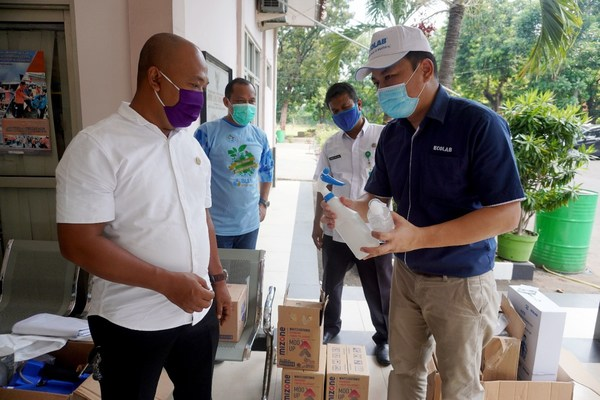 Rony Hutagalung from Ecolab Food and Beverage division, handing in-kind donations to Drs. Santoso, MA, Secretary of Gunung Putri District Government Office in West Java, Indonesia