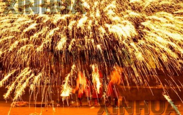 Tourists enjoying the cultural heritage performance Fire Dragon Steel Flower in the ancient town.