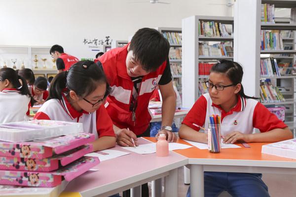 The volunteer of Infinitus MHO helps the children make hand-copied newspaper