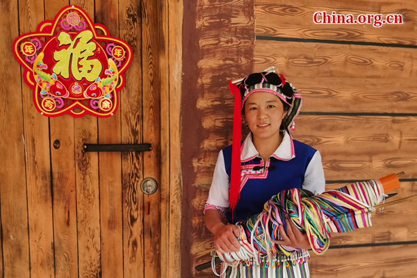 Ma Jinhua in Chala village, Yunnan province, stands beside her family-run homestay inn on May 20, 2021. [Photo by He Shan/China.org.cn]