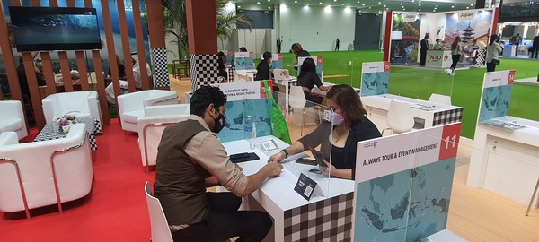 Indonesian destination's representative welcoming potential partners and tourists at one of the Indonesian Pavilion booth