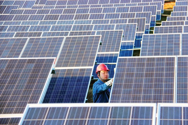 A technician of Pingqing Photovoltaic Power Station inspects solar panels in Weining in southwest China's Guizhou province. (Photo by Huan He)
