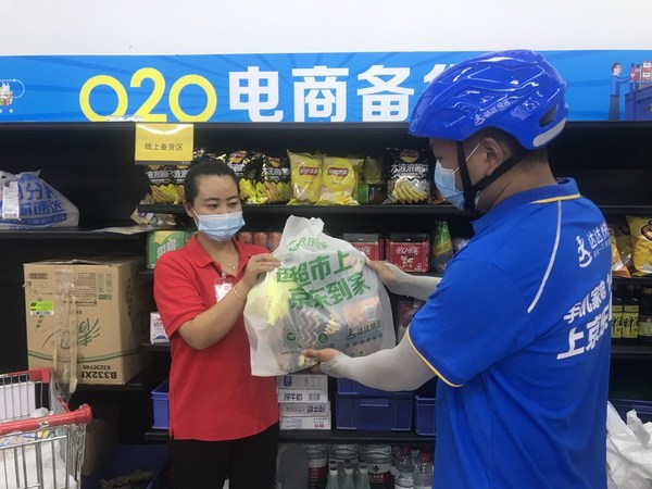 A Dada Now rider takes online orders for delivery at a CP Lotus store in Beijing