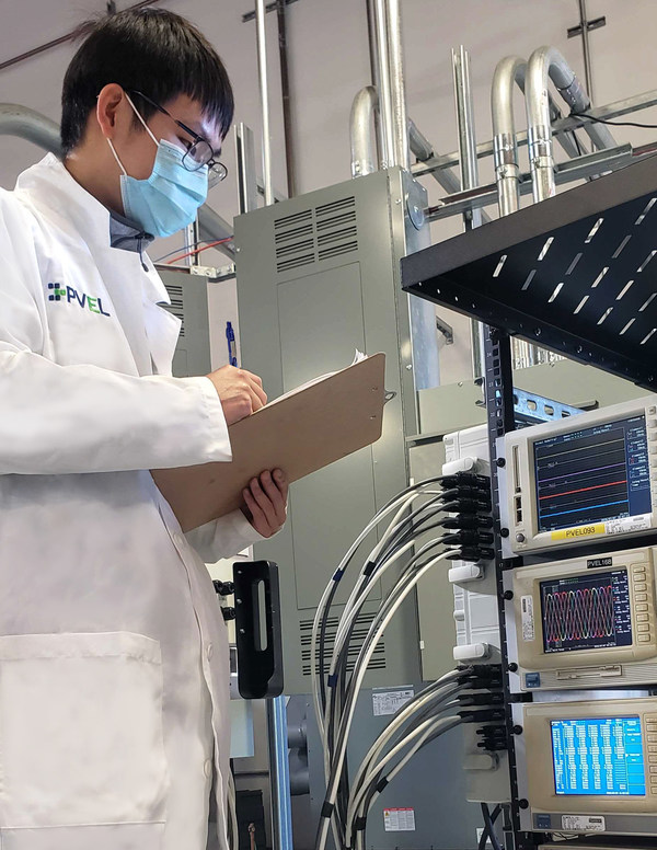A PVEL lab technician notes power measurements of a solar inverter