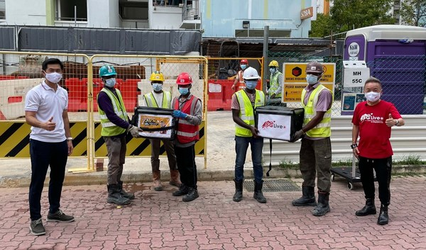 Mr Desmond Tan (Leftmost) with migrant workers at a Pasir Ris construction site, along with host Marcus Chin (Rightmost)